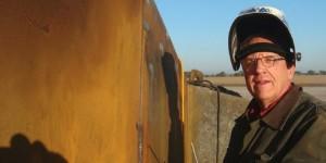Tom Barnes welding in the field