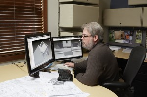 Scott Owen sitting at desk with project design open on computer monitor