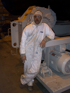 Dave in full paint suit leaning against machinery